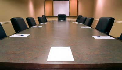 empty board room table with pens and paper