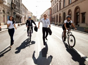 Businesspeople competing with bicycles and running in the city