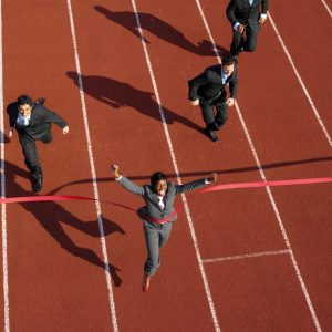 Businesswoman Crossing the Finish Line Ahead of Businessmen