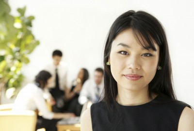 Business woman in office with out of focus office workers behind her