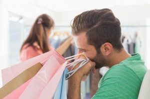 Bored man sitting with shopping bags while woman by clothes rack in the background