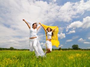 women skipping through grass