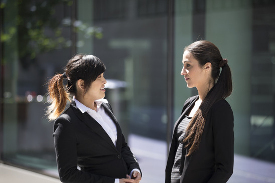 Two Happy Business women outside the office talking to each other, mentor