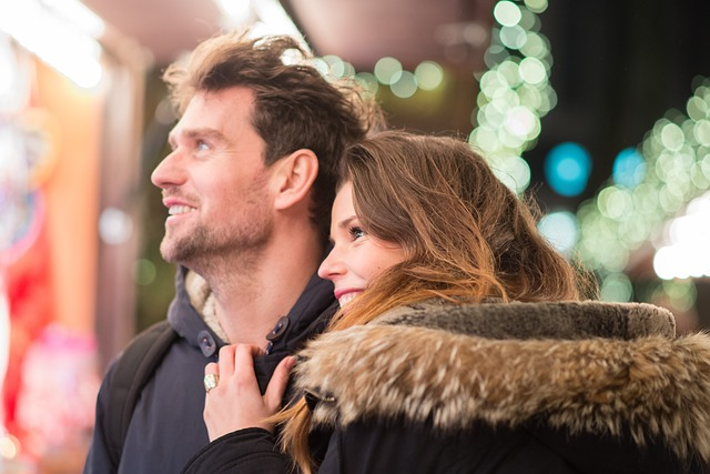 A couple smiling looking at a Christmas shop
