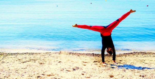 Woman doing cartwheels on the sand enjoying Body:ReSet retreat