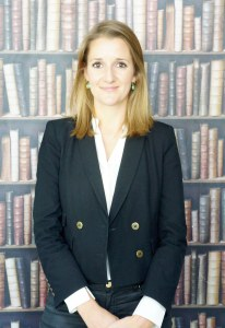 Marina Banks standing infront of a mural wall of books on a shelf in a black jacket