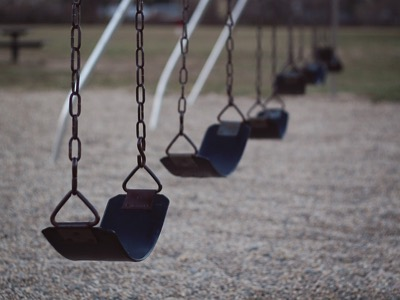 A set of empty black swings in a line