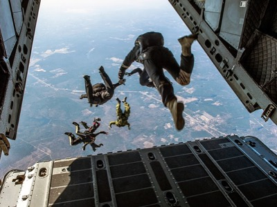 A group of people jumping out of the back of the plane to go skydiving