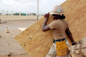 female apprenticeship construction worker carrying plank of wood