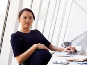 pregnant woman at her desk featured