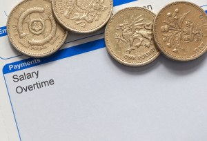 wage slip with pound coins, national minimum wage
