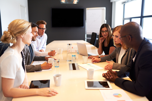 group of people meeting in a boardroom featured