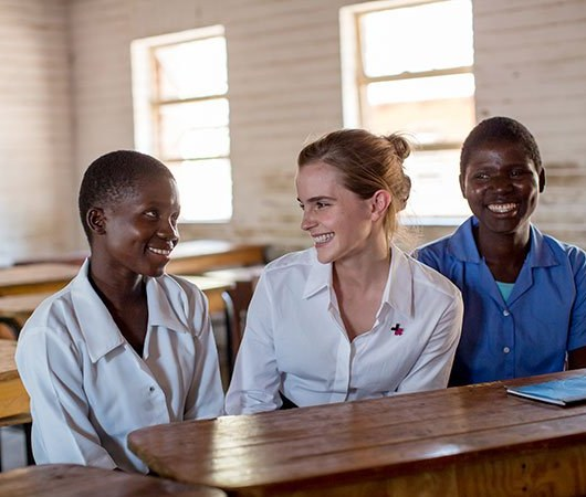 Emma Watson visiting a Malawi school and talking to two smiling girls