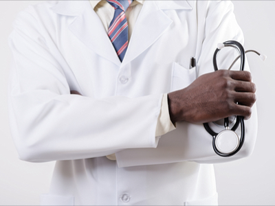 Arm and hand of a black doctor in a white lab coat holding an instrument